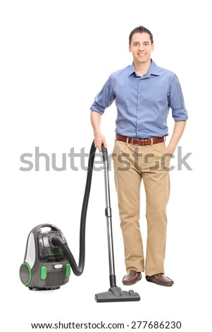 Full length portrait of a young casual man posing with a vacuum cleaner isolated on white background