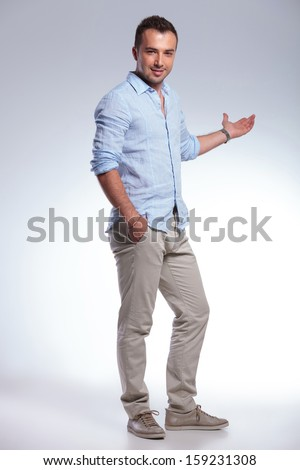 full length portrait of a young casual man presenting something in the back while holding a hand in his pocket and looking into the camera. on gray background - stock photo