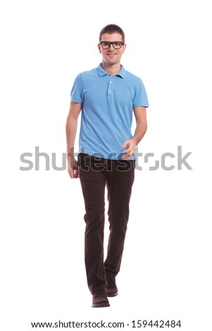 full length portrait of a young casual man walking toward the camera and smiling. on white background