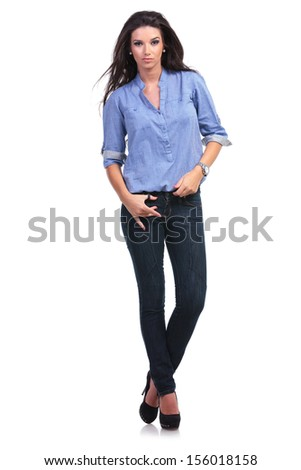 full length portrait of a young casual woman holding a thumb in a loop of her jeans while looking into the camera. on white background