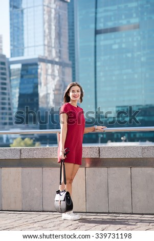 Full length portrait of a young charming woman with beautiful smile posing outdoors against skyscrapers, happy attractive female standing alone on the street near modern buildings in sunny summer day  - stock photo