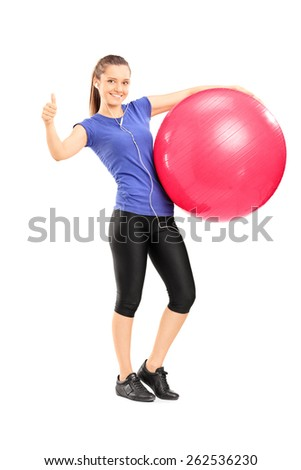 Full length portrait of a young cheerful woman holding an exercise ball and giving a thumb up isolated on white background - stock photo