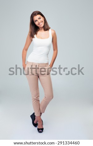 Full length portrait of a young cheerful woman standing over gray background - stock photo