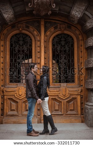 Full length portrait of a young couple flirting outdoors with old wooden door on background - stock photo