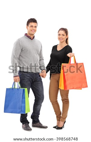 Full length portrait of a young couple holding shopping bags and looking at the camera isolated on white background