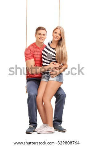 Full length portrait of a young couple sitting on a wooden swing together and looking at the camera isolated on white background - stock photo