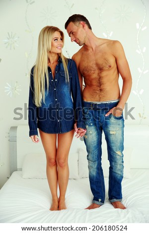 Full length portrait of a young couple standing on the bed and looking on each other  - stock photo