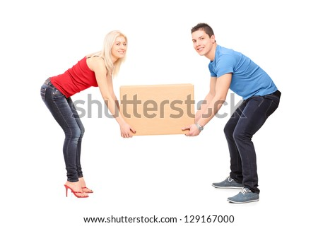 Full length portrait of a young couple trying to lift a box isolated against white background - stock photo