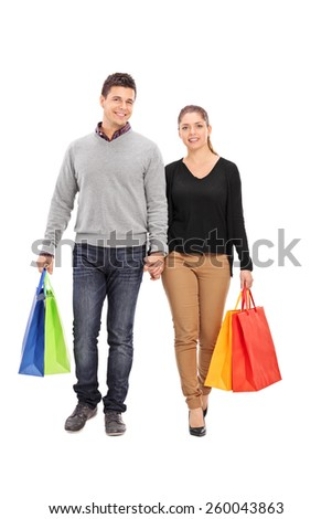 Full length portrait of a young couple walking with shopping bags isolated on white background
