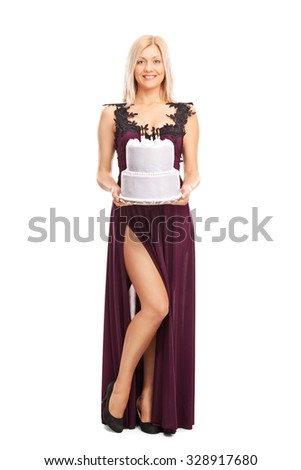 Full length portrait of a young elegant woman carrying a birthday cake and looking at the camera isolated on white background - stock photo