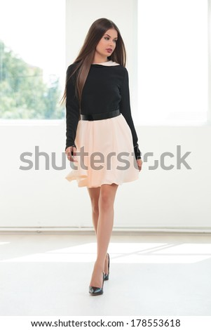 full length portrait of a young fashion woman walking toward the camera in a studio while looking away, to her side - stock photo