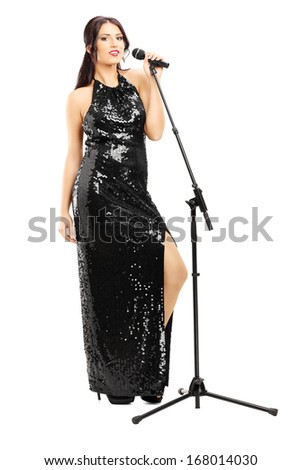 Full length portrait of a young female singer in black dress posing isolated on white background - stock photo