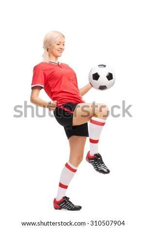 Full length portrait of a young female soccer player in a red jersey and black shorts juggling a football isolated on white background - stock photo
