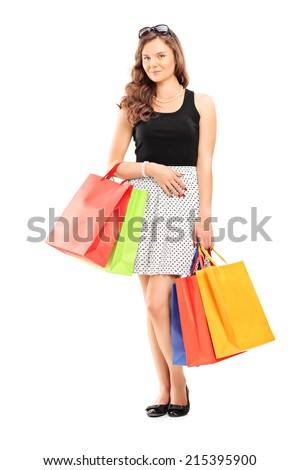 Full length portrait of a young girl holding shopping bags isolated on white background - stock photo