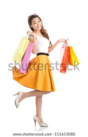 Full-length portrait of a young girl with many paperbags against a white background - stock photo