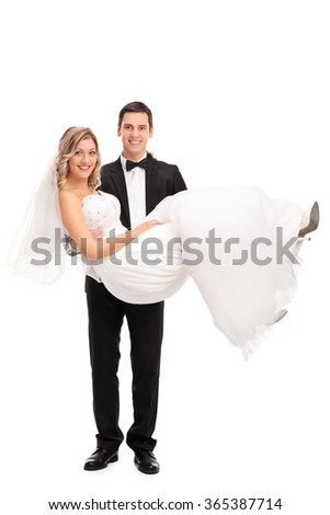 Full length portrait of a young groom carrying a bride in his hands isolated on white background  - stock photo