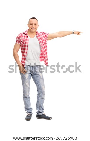 Full length portrait of a young guy in a checkered shirt pointing right with his hand isolated on white background