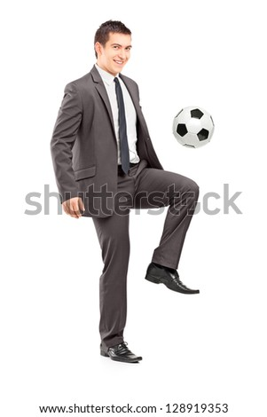 Full length portrait of a young handsome businessman kicking a football isolated on white background