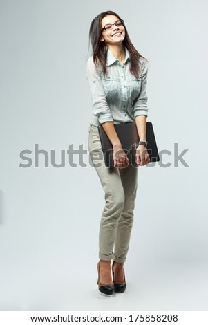 Full-length portrait of a young happy businesswoman holding laptop on gray background - stock photo