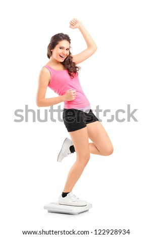 Full length portrait of a young happy female standiong on a weight scale isolated on white background - stock photo