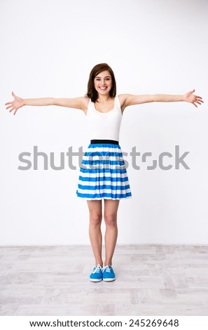 Full length portrait of a young happy girl glad to see you - stock photo
