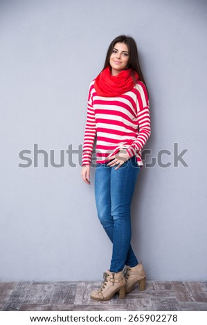Full length portrait of a young happy woman posing in studio. Looking at camera. Wearing in sweater, scarf and jeans.