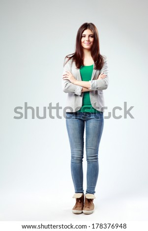 Full-length portrait of a young happy woman with arms folded on gray background - stock photo