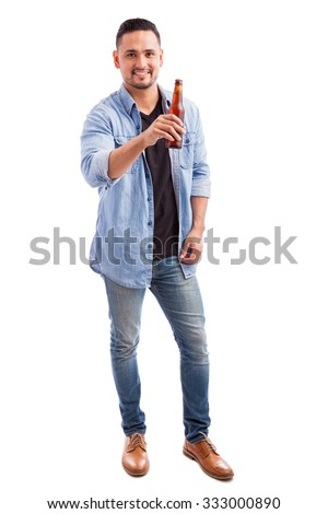 Full length portrait of a young Latin man drinking beer and raising his bottle to the camera in a white background - stock photo
