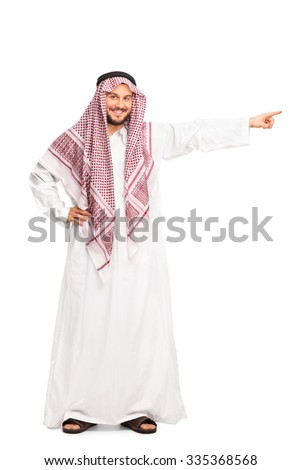 Full length portrait of a young male Arab in a white robe pointing right with his hand isolated on white background - stock photo