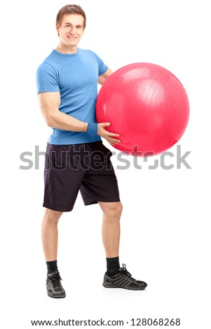 Full length portrait of a young male athlete holding a pilates ball isolated against white background - stock photo