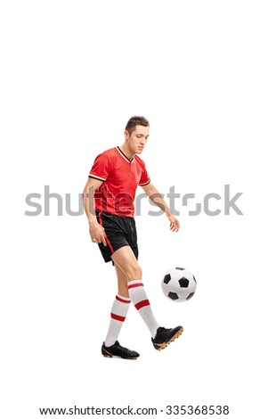 Full length portrait of a young male football player juggling a ball isolated on white background - stock photo