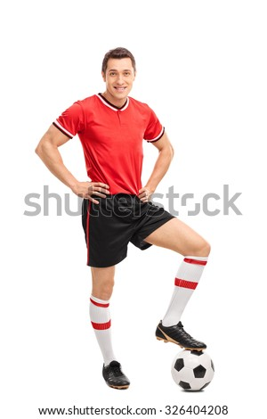 Full length portrait of a young male football player stepping over a ball and looking at the camera isolated on white background - stock photo