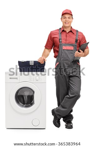 Full length portrait of a young male repairman holding a clipboard and standing next to a washing machine isolated on white background