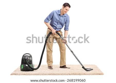 Full length portrait of a young man cleaning a carpet with a vacuum cleaner isolated on white background