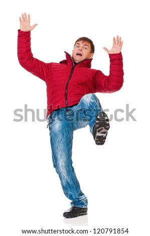 Full length portrait of a young man dressed with winter clothes slipping on floor isolated on white background - stock photo