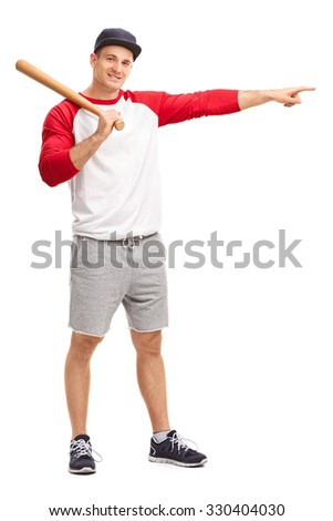 Full length portrait of a young man holding a baseball bat and pointing with his hand to the right isolated on white background - stock photo