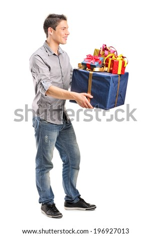 Full length portrait of a young man holding a bunch of presents isolated on white background