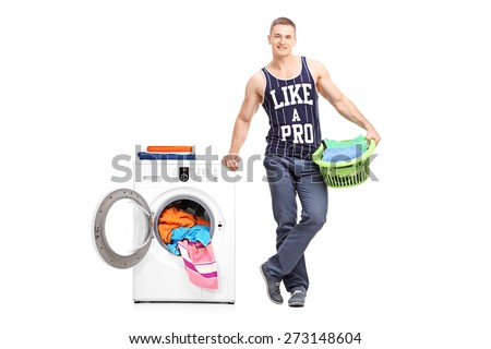 Full length portrait of a young man holding a laundry basket next to a washing machine isolated on white background - stock photo