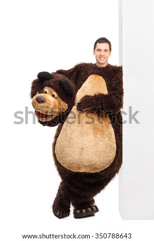 Full length portrait of a young man in a bear costume leaning against a wall and looking at the camera isolated on white background