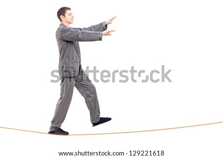 Full length portrait of a young man in pajamas sleepwalking on a rope isolated on white background - stock photo