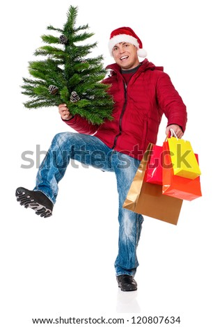 Full length portrait of a young man in winter clothing and Santa hat with shopping bags and artificial fir tree isolated on white background - stock photo