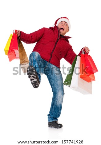 Full length portrait of a young man in winter clothing and Santa hat with shopping bags slipping on floor isolated on white background - stock photo