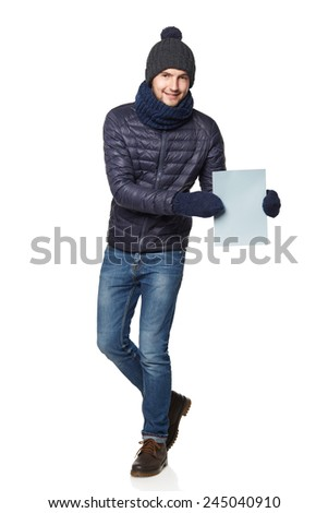Full length portrait of a young man in winter clothing with empty copy space for your text, isolated on white background - stock photo