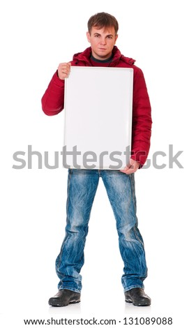 Full length portrait of a young man in winter clothing with empty white board isolated on white background - stock photo