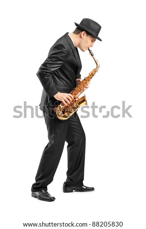 Full length portrait of a young man playing on saxophone isolated on background - stock photo