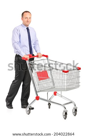 Full length portrait of a young man pushing a shopping cart isolated on white background - stock photo