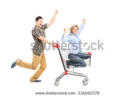 Full length portrait of a young man pushing a woman in a shopping cart isolated on white background - stock photo