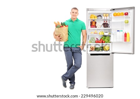 Full length portrait of a young man standing by an open refrigerator and holding a grocery bag isolated on white background - stock photo