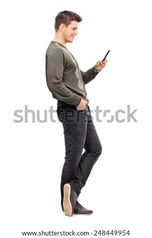 Full length portrait of a young man texting on his cell phone isolated on white background