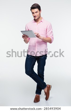 Full length portrait of a young man using tablet computer over gray background and looking at camera - stock photo